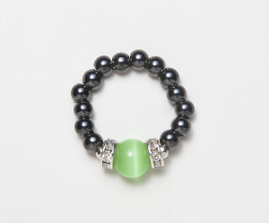 black beaded stretch ring with light green cats eye accent bead