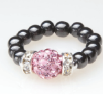 black beaded stretch ring with pink crystal accent bead